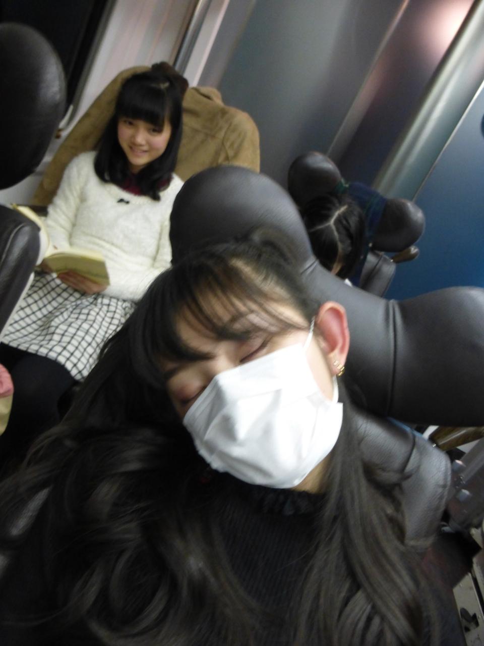 帰りの電車にて、すっかり遊び疲れた瀬田さん。その奥で勉強中(?)の西垣さん。(有彩/さくら)