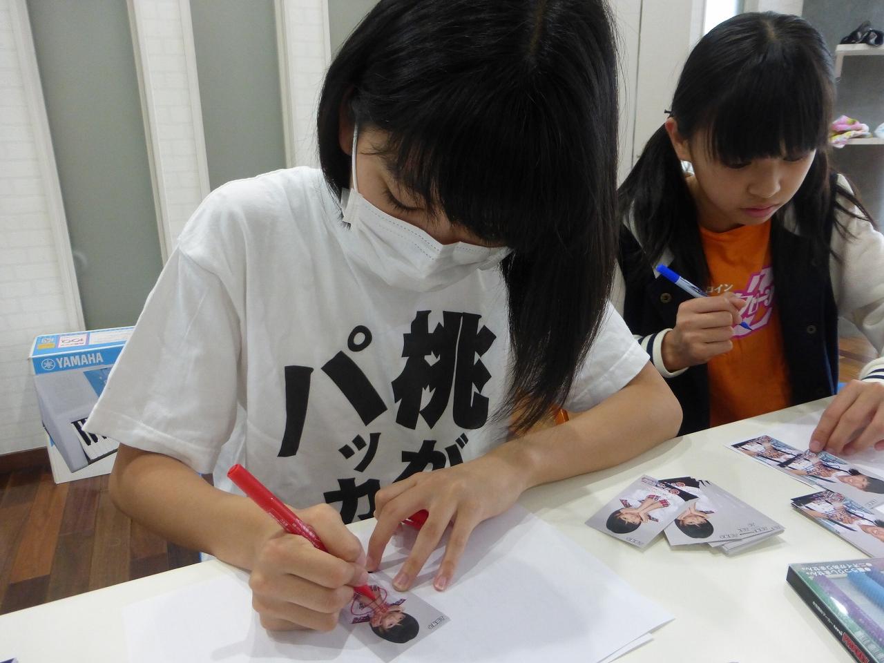 特典用の特性名刺にサイン書き(左:理子/右:蒼良)